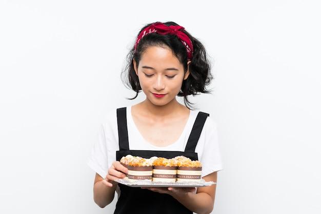 Молодая азиатская девушка держа много торта булочки над изолированной белой стеной