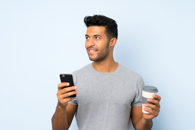何かを考えながら持ち帰るコーヒーと携帯電話を保持している孤立した壁の上の若いハンサムな男