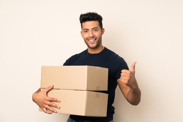 Молодой красавец над изолированной стеной, держа коробку, чтобы переместить его на другой сайт с большим пальцем вверх