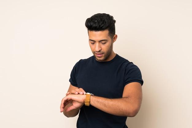 腕時計で孤立した壁の上の若いハンサムな男