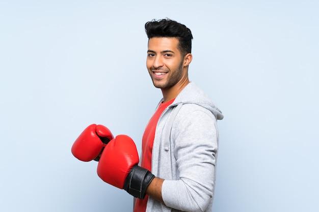 Спортивный человек с боксерскими перчатками над синей стеной
