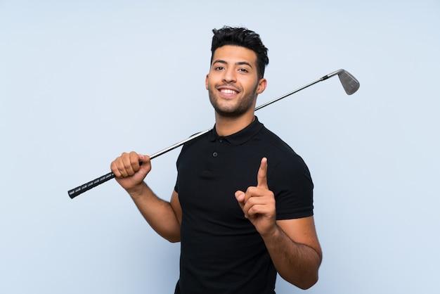 素晴らしいアイデアを指している分離の青い壁にゴルフをするハンサムな若い男