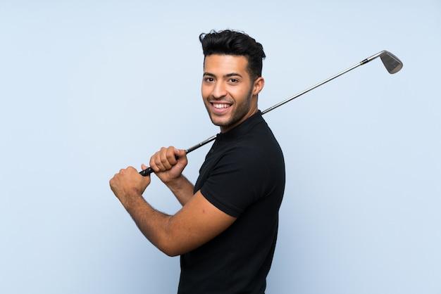 孤立した青い壁の上のゴルフハンサムな若い男