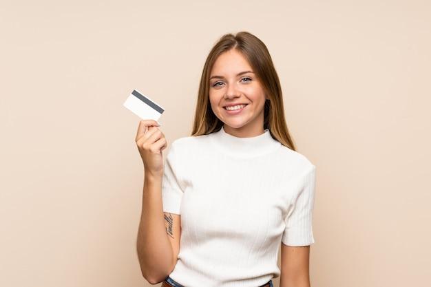 クレジットカードを保持している孤立した壁の上の若いブロンドの女性