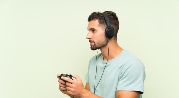 Молодой красавец, играя с контроллером видеоигры над изолированной зеленой стеной