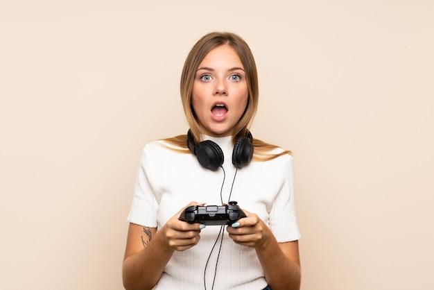 ビデオゲームで遊ぶ孤立した壁の上の若いブロンドの女性