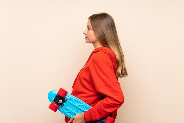 後ろの位置でスケートで孤立した壁の上の若いブロンドの女性