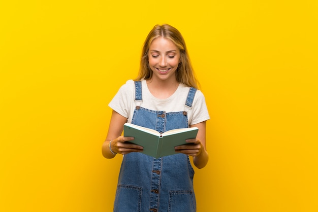 孤立した黄色の壁を押しながら本を読んで金髪の若い女性
