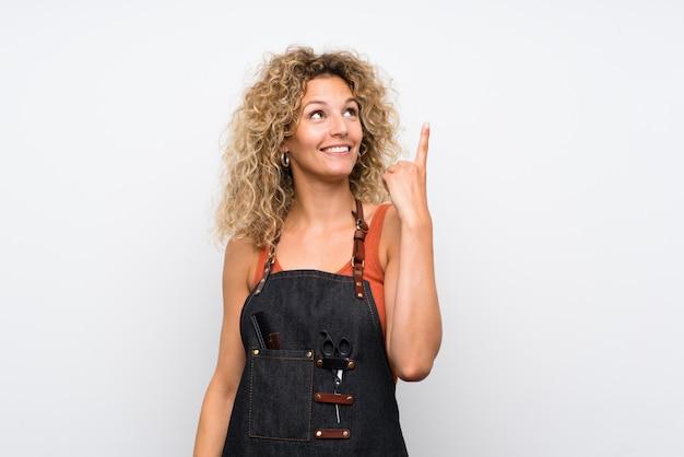 指を持ち上げながら解決策を実現しようとしている孤立した壁の上の若い美容師女性