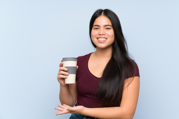 Девушка молодого подростка азиатская держа кофе взятия прочь