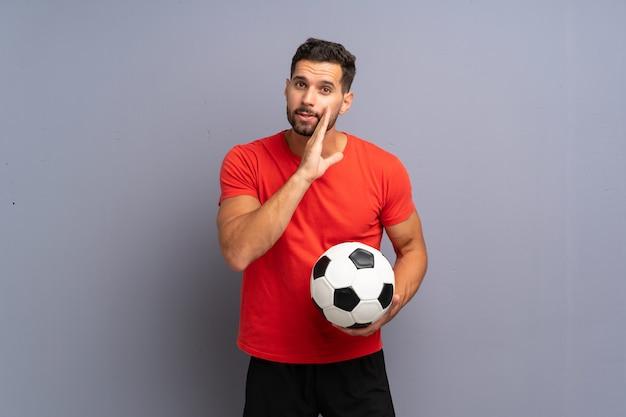 Красивый молодой футболист человек шепчет что-то