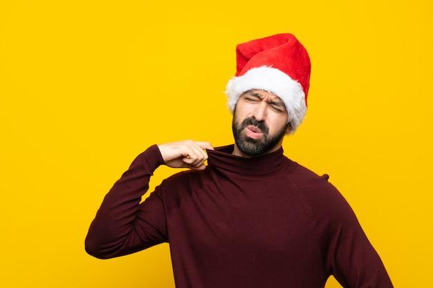 孤立した黄色の背景の上のクリスマス帽子で疲れた男