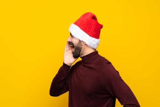 孤立した黄色の背景上で叫んでクリスマス帽子を持つ男