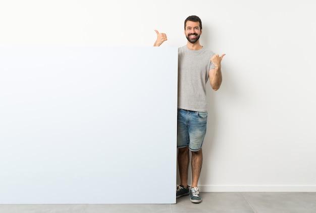 Человек с бородой, проведение большой синий пустой плакат с большими пальцами руки вверх