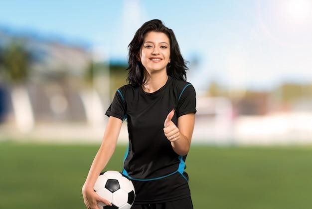 Молодой футболист женщина с большими пальцами руки вверх, потому что что-то хорошее произошло на открытом воздухе