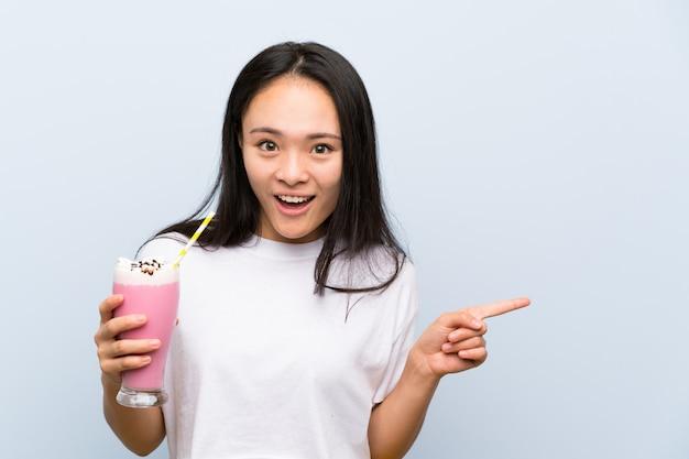 Девушка подростка азиатская держа удивленный молочный коктейль клубники и указывая палец в сторону