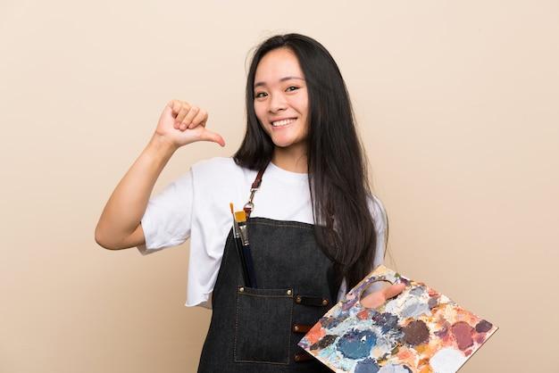 ティーンエイジャーの画家アジアの女の子の誇りと自己満足