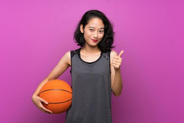 Молодая азиатская женщина играя баскетбол