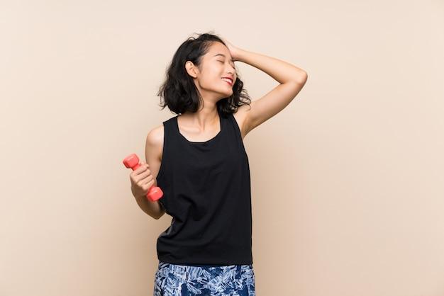 重量挙げを作る若いアジアの女の子は何かを実現し、解決策を意図