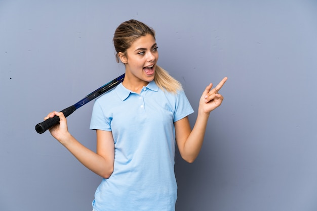 Девушка-теннисистка над серой стеной удивлена и указывает пальцем в сторону