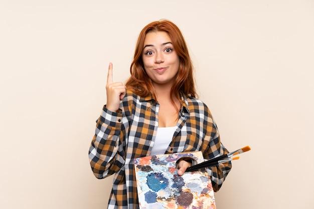 Девушка рыжего подростка держа палитру над изолированной стеной указывая указательным пальцем отличная идея