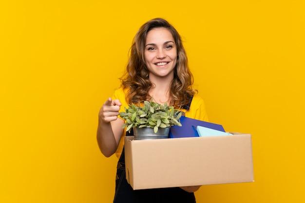 Молодая белокурая девушка делая движение пока поднимающ коробку полный вещей удивленных и указывающих фронт