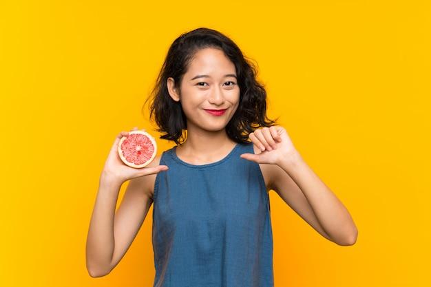 誇りに思って、自己満足のグレープフルーツを保持している若いアジアの女の子