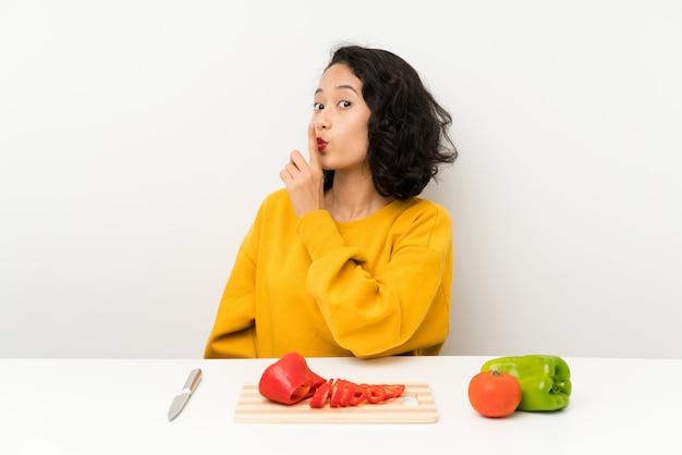沈黙のジェスチャーをしているテーブルの野菜と若いアジアの女の子