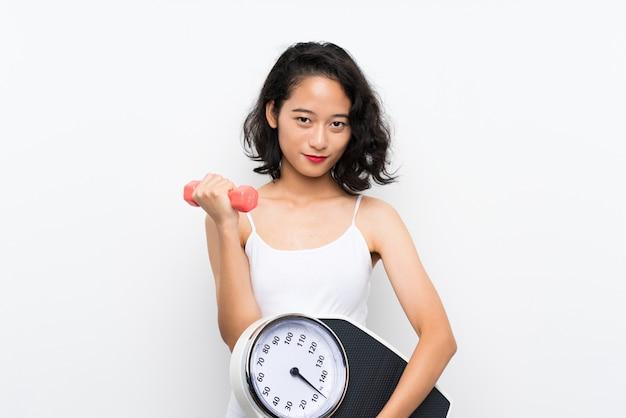 Молодая азиатская девушка делает тяжелую атлетику и с весами