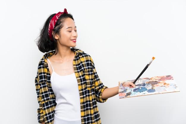 幸せな表情でパレットを保持している若いアーティストの女性