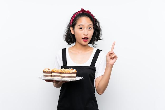 素晴らしいアイデアを指しているマフィンケーキの多くを保持している若いアジアの女の子