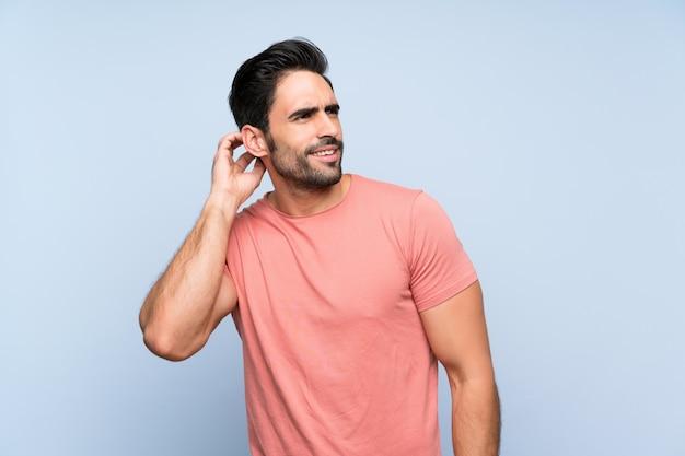 アイデアを考えてピンクのシャツでハンサムな若い男