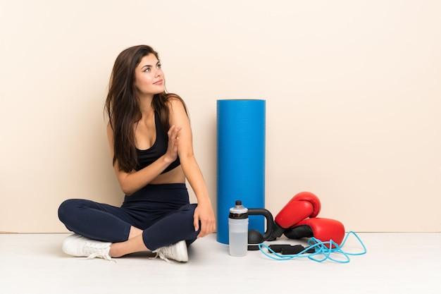 考えを考えて床に座ってティーンエイジャーのスポーツ少女
