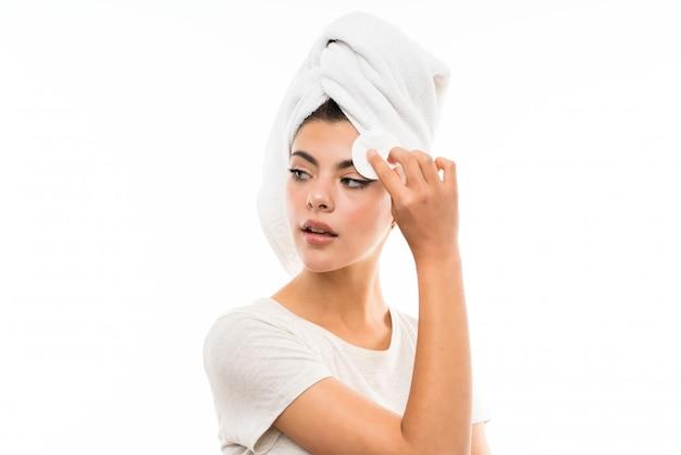 Девочка-подросток снимает макияж с лица с помощью ватного диска