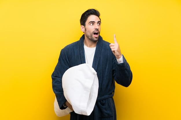 Красивый мужчина в пижаме, намереваясь реализовать решение, поднимая палец вверх