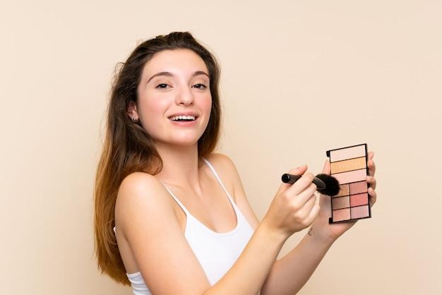 孤立した壁の上の化粧パレットと若いブルネットの少女