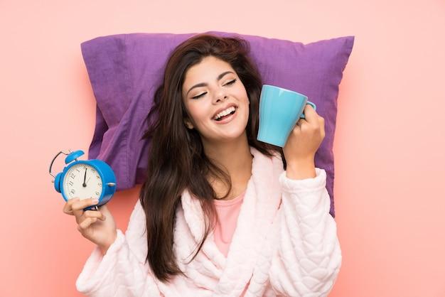 Девушка-подросток в халате на розовом фоне держит винтажные часы и держит чашку кофе