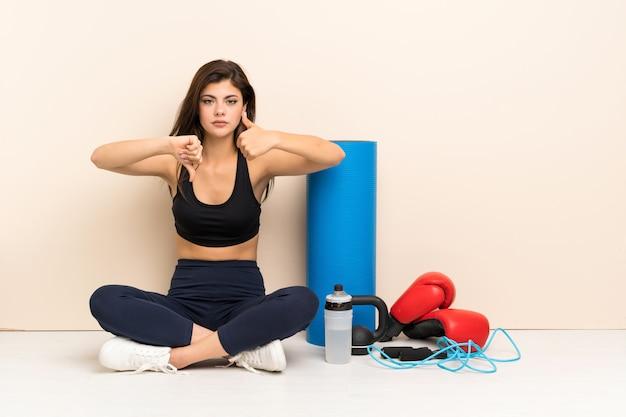 良い悪い兆候を作る床に座ってティーンエイジャーのスポーツ少女。はいかどうかは未定