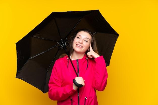 解決策を実現しようとしている孤立した黄色の壁に傘を置く若いブルネットの少女