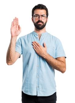青い眼鏡をした宣誓をするハンサムな男