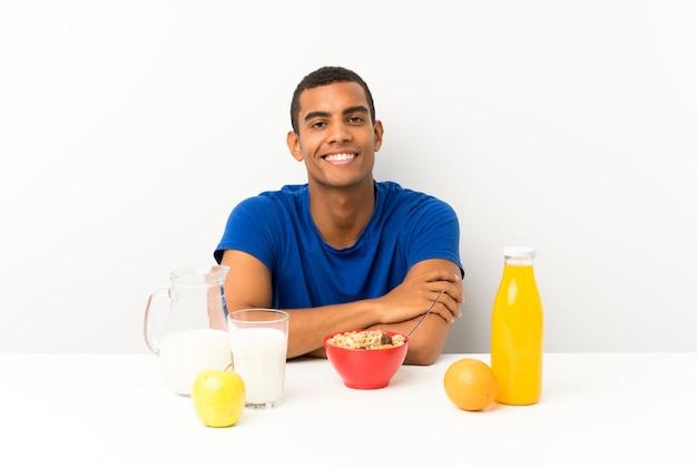 笑っているテーブルで朝食を持っている若い男