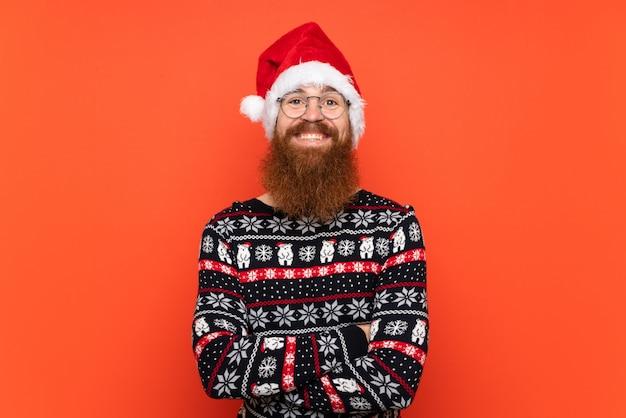 Рождественский человек с длинной бородой над изолированной красной стеной много улыбается