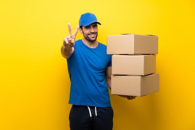 Молодой доставщик улыбается и показывает знак победы