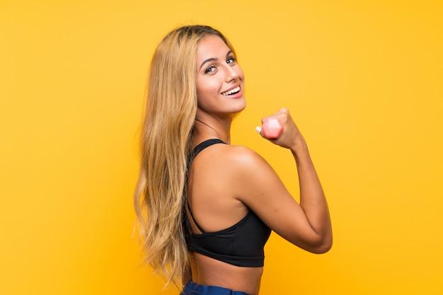 孤立した壁を越えて重量挙げを作る若いスポーツ女性