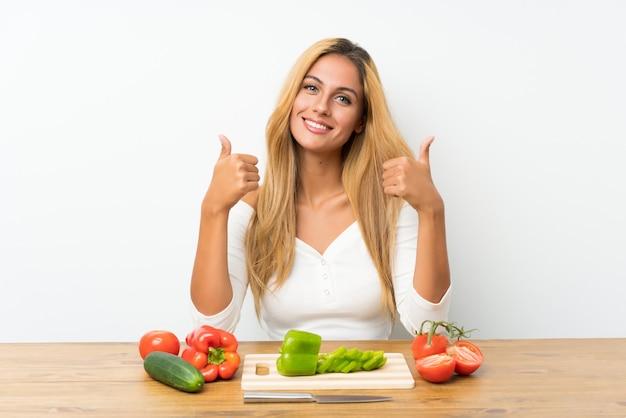 Молодая блондинка с овощами в таблице, давая недурно жест