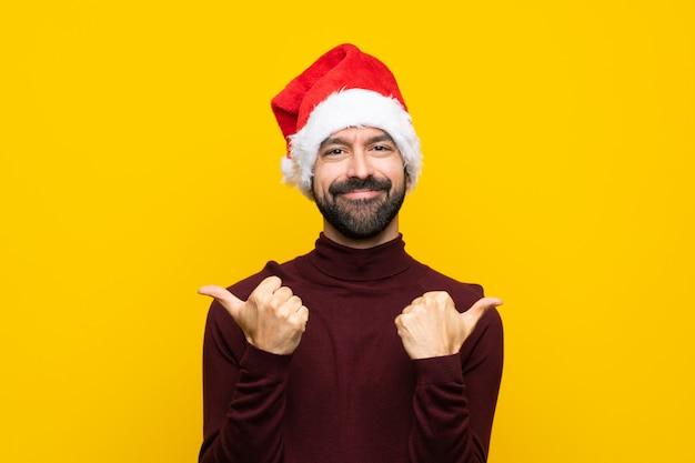 ジェスチャーと笑みを浮かべて親指で孤立した黄色の壁の上のクリスマス帽子を持つ男