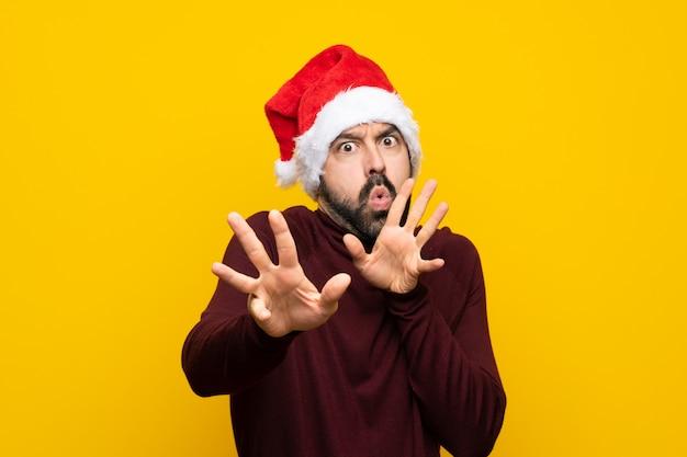 孤立した黄色の壁の前に手を伸ばして緊張のクリスマス帽子を持つ男
