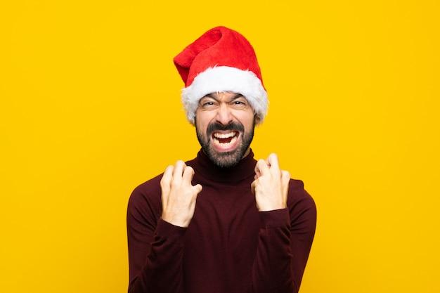 悪い状況に不満の孤立した黄色の壁の上のクリスマス帽子の男