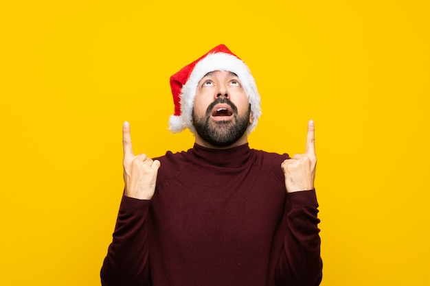 Человек с рождественской шляпой над изолированной желтой стеной удивлен и направлен вверх