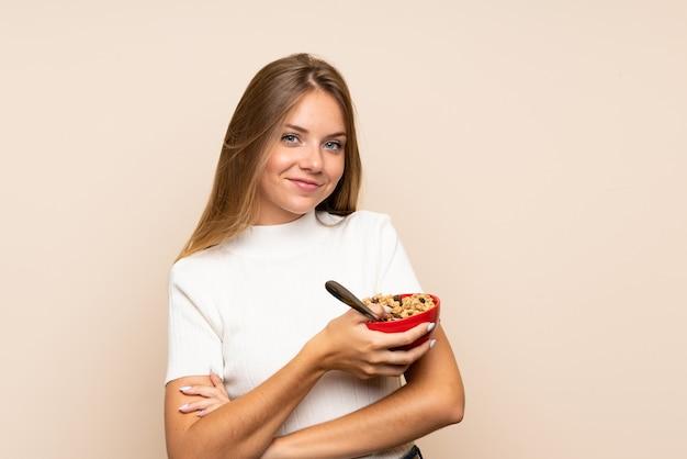 穀物のボウルを保持している若いブロンドの女性